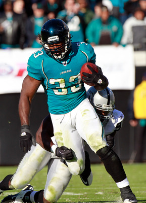 JACKSONVILLE, FL - DECEMBER 12:  Greg Jones #33 of the Jacksonvile Jaguars breaks the tackle of Kamerion Wimbley #96 of the Oaklnad Raiders during the game at EverBank Field on December 12, 2010 in Jacksonville, Florida.  (Photo by Sam Greenwood/Getty Ima