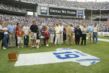 BALTIMORE - SEPTEMBER  15:  Family and friends pay tribute to Johnny Unitas as they stand behind a jersey painted with his name and uniform number on the grass prior to the game between the Tampa Bay Buccaneers and the Baltimore Ravens on September 15, 20