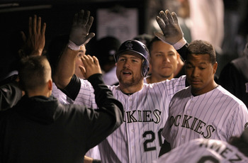 DENVER, CO - MAY 09:  Cacther Chris Iannetta #20 of the Colorado Rockies celebrates in the dugout after his solo homerun off of starting pitcher Chris Capuano #38 of the New York Mets to give the Rockies a 2-1 lead in the seventh inning at Coors Field on