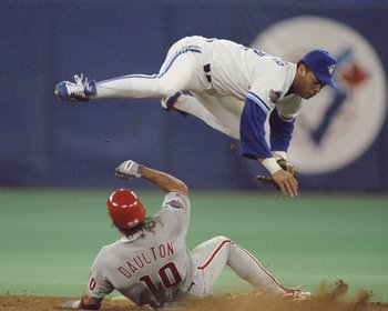 17 Oct 1993:  Second baseman Roberto Alomar of the Toronto Blue Jays jumps over Phillies Catcher Darren Daulton #10 sliding into second base to avoid the collision after throwing the ball to first base during the 1993 World Series Game 2 against the Phila