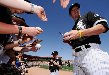 GLENDALE, AZ - MARCH 11:  Jake Peavy #44 of the Chicago White Sox and his son Wyatt sign baseballs prior to the start of the spring training baseball game against  Chicago Cubs at Camelback Ranch on March 11, 2011 in Glendale, Arizona.  (Photo by Kevork D