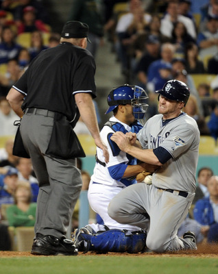LOS ANGELES, CA - APRIL 30:  Chase Headley #7 of the San Diego Padres knocks the ball away from Rod Barajas #28 of the Los Angeles Dodgers in front outfield home plate umpire Bob Davidson to score a run for a 5-2 lead during the eighth inning at Dodger St