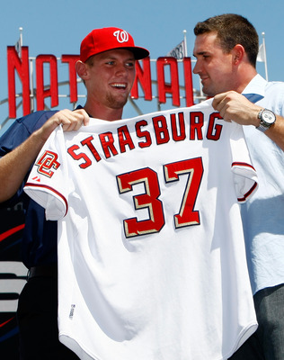 WASHINGTON - AUGUST 21:  Stephen Strasburg (L), the overall first pick in the 2009 MLB Draft, is presented with his jersey by Nationals third baseman Ryan Zimmerman (R) after being introduced at Nationals Park August 21, 2009 in Washington, DC. Strasburg,