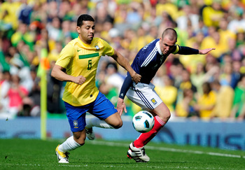 LONDON, ENGLAND - MARCH 27:  Andre Santos of Brazil fights for the ball with Kenny Miller of Scotland during the International friendly match between Brazil and Scotland at Emirates Stadium on March 27, 2011 in London, England.  (Photo by Jamie McDonald/G
