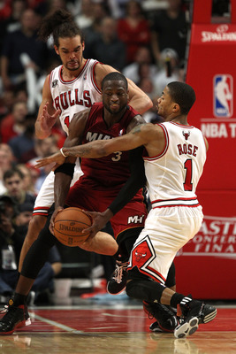 CHICAGO, IL - MAY 18:  Dwyane Wade #3 of the Miami Heat looks to pass as he is defended by Derrick Rose #1 and Joakim Noah #13 of the Chicago Bulls in Game Two of the Eastern Conference Finals during the 2011 NBA Playoffs on May 18, 2011 at the United Cen