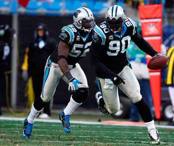 CHARLOTTE, NC - JANUARY 03:  Julius Peppers #90 of the Carolina Panthers runs with the ball alongside teammate Jon Beason #52 after an interception against the New Orleans Saints in the second half of the game at Bank of America Stadium on January 3, 2010