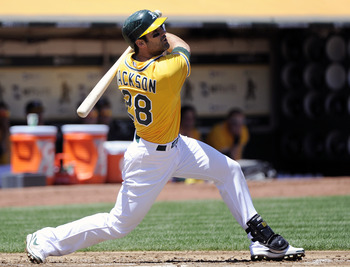 OAKLAND, CA - MAY 1: Conor Jackson #28 of the Oakland Athletics hits a double to drive in two runs in the bottom of the first inning against the Texas Rangers during a MLB baseball game at the Oakland-Alameda County Coliseum May 1, 2011 in Oakland, Califo