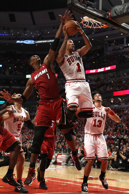 CHICAGO, IL - MAY 18:  Derrick Rose #1 of the Chicago Bulls drives for a shot attempt against Chris Bosh #1 of the Miami Heat in Game Two of the Eastern Conference Finals during the 2011 NBA Playoffs on May 18, 2011 at the United Center in Chicago, Illino