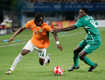 QINHUANGDAO, CHINA - AUGUST 16:  Gervinho of Ivory Coast and Ebenezer Ajilore of Nigeria  compete for the ball during the Men's Quarter Final match between Nigeria and Ivory Coast at Qinhuangdao Olympic Sports Center Stadium on Day 8 of the Beijing 2008 O