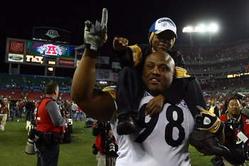 TAMPA, FL - FEBRUARY 01:  Defensive tackle Casey Hampton #98 of the Pittsburgh Steelers celebrates with child after their 27-23 win against the Arizona Cardinals during Super Bowl XLIII on February 1, 2009 at Raymond James Stadium in Tampa, Florida.  (Pho