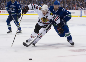VANCOUVER, CANADA - APRIL 26: Keith Ballard #4 of the Vancouver Canucks and Jonathan Toews #19 of the Chicago Blackhawks battle for the loose puck during the first period in Game Seven of the Western Conference Quarterfinals during the 2011 NHL Stanley Cu