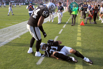 OAKLAND, CA - OCTOBER 31:  Michael Huff #24 checks on injured teammate Nnamdi Asomugha #21 of the Oakland Raiders during their game against the Seattle Seahawks at Oakland-Alameda County Coliseum on October 31, 2010 in Oakland, California.  (Photo by Ezra