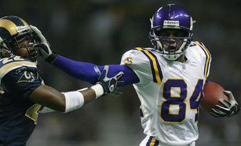 ST. LOUIS - NOVEMBER 30:  Randy Moss #84 of the Minnesota Vikings stiff arms Travis Fisher #22 of the St. Louis Rams on November 30, 2003 at the Edward Jones Dome in St. Louis, Missouri. The Rams defeated the Vikings 48-17.  (Photo by Elsa/Getty Images)