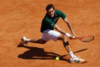 ROME, ITALY - MAY 13:  Marin Cilic of Croatia slides to play a backhand during his quarter final match against Rafael Nadal of Spain during day six of the Internazoinali BNL D'Italia at the Foro Italico Tennis Centre  on May 13, 2011 in Rome, Italy.  (Pho