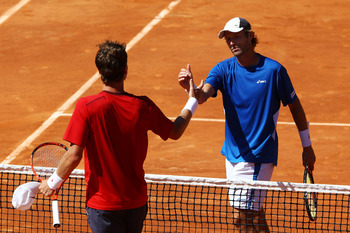 PARIS, FRANCE - MAY 23:  Stephane Robert (R) of France shakes hands with Tomas Berdych of Czech Republic as he celebrates victory in their men's singles round one match on day two of the French Open at Roland Garros on May 23, 2011 in Paris, France.  (Pho