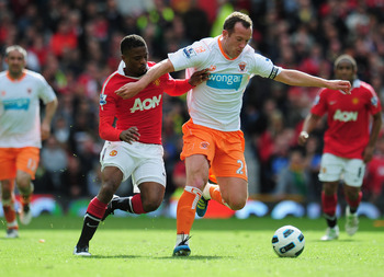 MANCHESTER, ENGLAND - MAY 22:  Charlie Adam of Balckpool battles with Patrice Evra of Manchester United during the Barclays Premier League match between Manchester United and Blackpool at Old Trafford on May 22, 2011 in Manchester, England.  (Photo by Sha