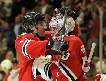 CHICAGO, IL - MARCH 23: Chris Campoli #14 and Corey Crawford #50 of the Chicago Blackhawks celebrate their win over the Florida Panthers at the United Center on March 23, 2011 in Chicago, Illinois. The Blackhawks defeated the Panthers 4-0.  (Photo by Bruc