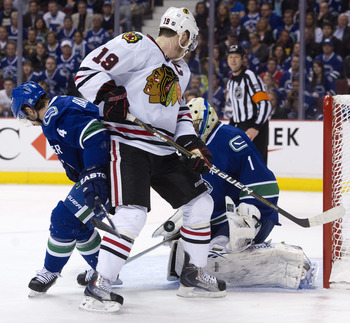 VANCOUVER, CANADA - APRIL 26: Goalie Roberto Luongo #1 of the Vancouver Canucks makes a save while Jonathan Toews #19 of the Chicago Blackhawks and Keith Ballard #4 of the Vancouver Canucks  battle for position in front of the net during the first period
