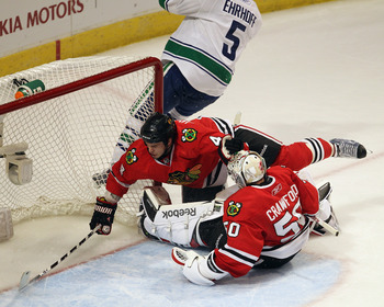 CHICAGO, IL - APRIL 19: Niklas Hjalmarsson #4 of the Chicago Blackhawks is pushed over teammate Corey Crawford #50 by Christian Ehrhoff #5 of the Vancouver Canucks in Game Four of the Western Conference Quarterfinals during the 2011 NHL Stanley Cup Playof