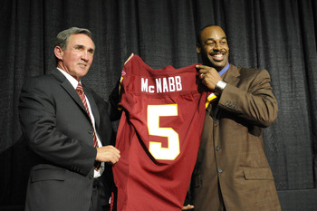 ASHURN, VA - APRIL 6:  Mike Shanahan, head coach of the Washington Redskins presents Donovan McNabb with his new jersey during a press conference on April 6, 2010 at Redskin Park in Ashburn, Virginia.  (Photo by Mitchell Layton/Getty Images)