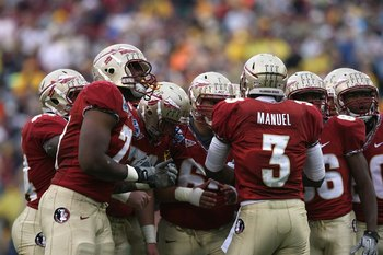 JACKSONVILLE, FL - JANUARY 01:  Quarterback E.J. Manuel #3 of the Florida State Seminoles calls out a play in the huddle against the West Virginia Mountaineers during the Konica Minolta Gator Bowl on January 1, 2010 at Jacksonville Municipal Stadium in Ja