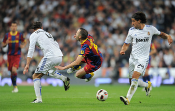 MADRID, SPAIN - APRIL 16:  Andres Iniesta (C) of Barcelona is fouled by Sergio Ramos (L) of Real Madrid as Sami Khedira of Real Madrid looks on during the la Liga match between Real Madrid and Barcelona at Estadio Santiago Bernabeu on April 16, 2011 in Ma