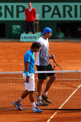 PARIS, FRANCE - MAY 24:  Rafael Nadal (L) of Spain meets John Isner of USA at the net after their men's singles round one match on day three of the French Open at Roland Garros on May 24, 2011 in Paris, France.  (Photo by Clive Brunskill/Getty Images)