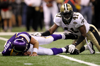 NEW ORLEANS - SEPTEMBER 09:  Quarterback Brett Favre #4 of the Minnesota Vikings lies on the turf after taking a hard hit from Roman Harper #41 of the New Orleans Saints at Louisiana Superdome on September 9, 2010 in New Orleans, Louisiana.  (Photo by Ron