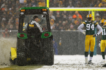 GREEN BAY, WI - JANUARY 12:  Defensive end Kabeer Gbaja-Biamila #94 of the Green Bay Packers watches as a snow plow drives down the middle of the field in the fourth quarter of the game against the Seattle Seahawks during the NFC divisional playoff game o