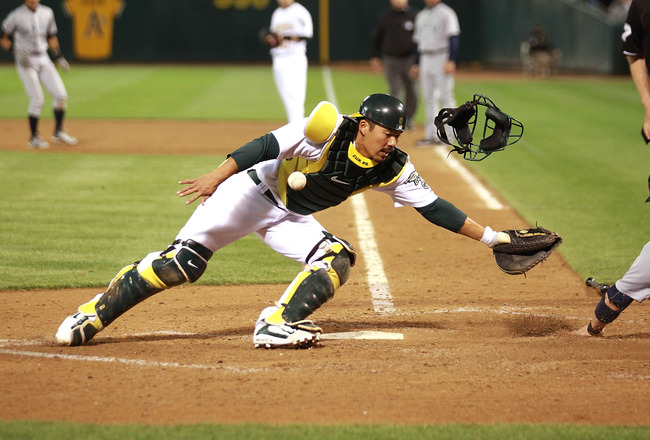 OAKLAND, CA - APRIL 01:  Kurt Suzuki #8 of the Oakland Athletics fails to tag out Brendan Ryan #26 of the Seattle Mariners on a single hit by Ichiro Suzuki during an opening day game of Major League Baseball at the Oakland-Alameda County Coliseum on April