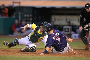 OAKLAND, CA - JUNE 04:  Joe Mauer #7 of the Minnesota Twins scores past Kurt Suzuki #8 of the Oakland Athletics on a single hit by Jason Kubel in the sixth inning during an MLB game at the Oakland-Alameda County Coliseum on June 4, 2010 in Oakland, Califo