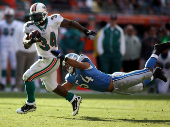 MIAMI - DECEMBER 26:  Running back Ricky Williams #34 of the Miami Dolphins breaks away from linebacker DeAndre Levy #54 of the Detroit Lions at Sun Life Stadium on December 26, 2010 in Miami, Florida. The Lions defeated the Dolphins 34-27.  (Photo by Mar