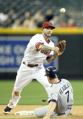 PHOENIX, AZ - MAY 16:  Infielder Ryan Roberts #14 of the Arizona Diamondbacks throws over the sliding Chase Headley #7 of the San Diego Padres attempting a double play during the seventh inning of the Major League Baseball game at Chase Field on May 16, 2