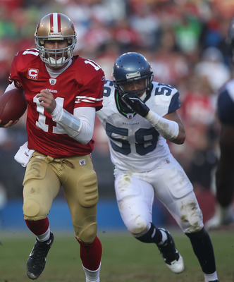 SAN FRANCISCO - DECEMBER 12:    Alex Smith #11 of the San Francisco 49ers runs with the ball against Dexter Davis #58 of the Seattle Seahawks during an NFL game at Candlestick Park on December 12, 2010 in San Francisco, California.  (Photo by Jed Jacobsoh