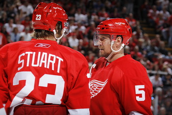 DETROIT - MAY 6: Brad Stuart #23 and Nicklas Lidstrom #5 of the Detroit Red Wings talk while playing the San Jose Sharks in Game Four of the Western Conference Semifinals during the 2011 NHL Stanley Cup Playoffs on May 6, 2011 at Joe Louis Arena in Detroi