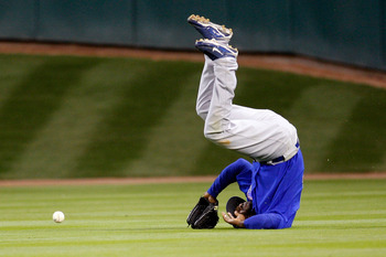 HOUSTON - APRIL 06:  Milton Bradley #21 of the Chicago Cubs flips over after missing a fly ball against the Houston Astros on Opening Day on April 6, 2009 at Minute Maid Park in Houston, Texas.  The Cubs defeated the Astros 4-2.  (Photo by Chris Graythen/