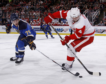 DETROIT, MI - MARCH 30: Jakub Kindl #4 of the Detroit Red Wings tries to keep the puck from the stick of Adam Cracknell #79 of the St. Louis Blues at Joe Louis Arena on March 30, 2011 in Detroit, Michigan.  (Photo by Gregory Shamus/Getty Images)