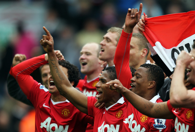 BLACKBURN, ENGLAND - MAY 14:  Fabio, Antonio Valencia and Patrice Evra of Manchester United celebrate after drawing the Barclays Premier League match between Blackburn Rovers and Manchester United but winning the title at Ewood park on May 14, 2011 in Bla