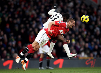 MANCHESTER, ENGLAND - DECEMBER 26: Nemanja Vidic of Manchester United heads clear under pressure from Asamoah Gyan of Sunderland during the Barclays Premier League match between Manchester United and Sunderland at Old Trafford on December 26, 2010 in Manc