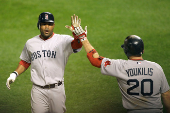 BALTIMORE, MD - APRIL 28: Carl Crawford #13 of the Boston Red Sox (L) celebrates with teammate Kevin Youkilis #20 after scoring against the Baltimore Orioles during the seventh inning at Oriole Park at Camden Yards on April 28, 2011 in Baltimore, Maryland