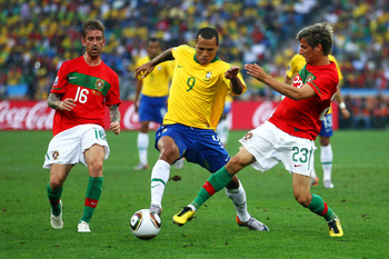 DURBAN, SOUTH AFRICA - JUNE 25: Luis Fabiano of Brazil is challenged by Raul Meireles (L) and Fabio Coentrao (R) of Portugal during the 2010 FIFA World Cup South Africa Group G match between Portugal and Brazil at Durban Stadium on June 25, 2010 in Durban