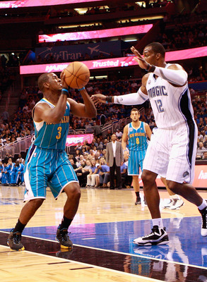 ORLANDO, FL - OCTOBER 10:  Chris Paul #3 of the New Orleans Hornets attempts a shot against Dwight Howard #12 of the Orlando Magic during the game at Amway Arena on October 10, 2010 in Orlando, Florida. NOTE TO USER: User expressly acknowledges and agrees