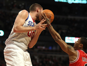 CHICAGO, IL - MARCH 28: Derrick Rose #1 of the Chicago Bulls reaches for the ball going off of the face of Spencer Hawes #00 of the Philadelphia 76ers at the United Center on March 28, 2011 in Chicago, Illinois. NOTE TO USER: User expressly acknowledges a