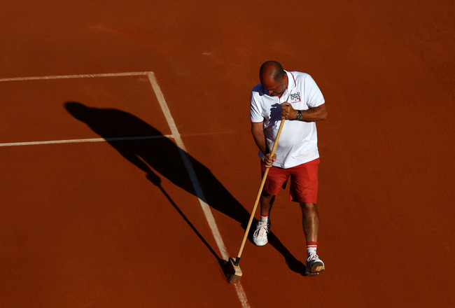 PARIS, FRANCE - MAY 25:  A member of the ground staff sweeps clay dust from the court lines during a break in the women's singles round two match between Vesna Dolonts of Russia and Francesca Schiavone of Italy on day four of the French Open at Roland Gar