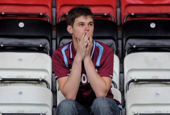 WIGAN, ENGLAND - MAY 15:  A West Ham United fan looks dejected following his team's relegation at the end of the Barclays Premier League match between Wigan Athletic and West Ham United at the DW Stadium on May 15, 2011 in Wigan, England.  (Photo by Chris