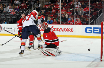 NEWARK, NJ - FEBRUARY 04: Michael Frolik #67 of the Florida Panthers sets up a screen as Johan Hedberg #1 of the New Jersey Devils surrenders a first period goal to Dennis Wideman (not pictured) at the Prudential Center on February 4, 2011 in Newark, New
