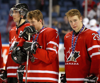 BUFFALO, NY - JANUARY 05: Jared Cowen #2, Sean Couturier #7 and Carter Ashton #25 of Canada stand on the ice during medal ceremonies after losing to Russia 5-3 during the 2011 IIHF World U20 Championship Gold medal game between Canada and Russia at the HS