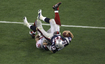 GLENDALE, AZ - FEBRUARY 03:  Quarterback Tom Brady #12 of the New England Patriots lies on his back after being sacked by defensive end Michael Strahan #92 of the New York Giants in the third quarter during Super Bowl XLII on February 3, 2008 at the Unive
