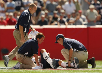 FOXBORO, MA - SEPTEMBER 7:  Quarterback Tom Brady #12 of the New England Patriots is assesed by the medical staff after he sustained an injury to his left knee in the first quarter against the Kansas City Chiefs at Gillette Stadium September 7, 2008 in Fo