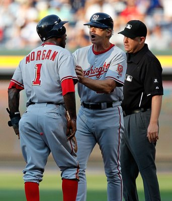ATLANTA - JUNE 28:  Dan Radison #53 of the Washington Nationals holds back Nyjer Morgan #1 in the first inning from arguing with first base umpire James Hoye #92 (right) after being tagged out at first base against the Atlanta Braves at Turner Field on Ju
